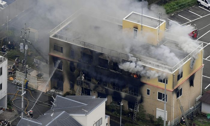 An aerial view shows firefighters battling fires at the site where a man started a fire after spraying a liquid at a three-story studio of Kyoto Animation Co. in Kyoto, western Japan, on July 18, 2019. (Kyodo/Reuters)