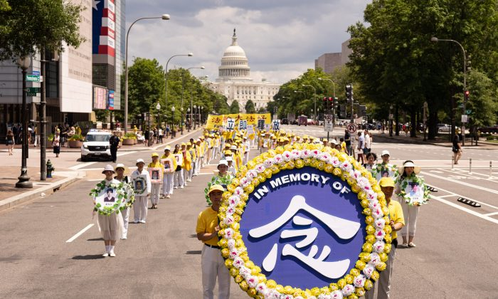 Falun Gong practitioners march from the U.S. Capitol to the Washington Monument to commemorate the 20th anniversary of Chinse regime's persecution of the practice on July 18, 2019. (Larry Dye/The Epoch Times)
