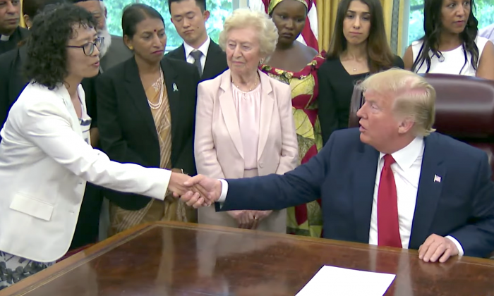 President Donald Trump shakes hands with Zhang Yuhua, a Falun Gong practitioner who survived persecution in China, at the White House on July 17, 2019. (Screenshot/The White House)