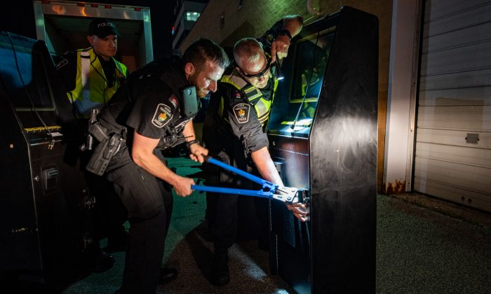 Officers with the York Regional Police work on dismantling a gaming machine at a mafia-owned location as part of a massive organized crime raid on July 12, 2019. (York Regional Police)
