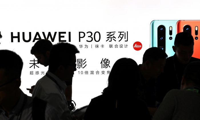 People visit a Huawei stand at the Shanghai New International Expo Centre in Shanghai on June 26, 2019. (Hector Retamal/AFP/Getty Images)