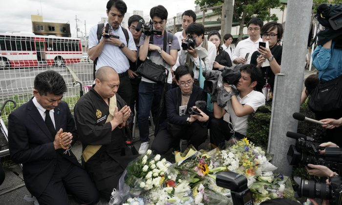 Japanese Diet member, Kenta Izumi (L), and Buddhist monk, Matsumoto Genkun, pay respects at a makeshift memorial site in front of burned Kyoto Animation Studio, in Kyoto, Japan, on July 19, 2019. (Jae C. Hong/AP Photo)