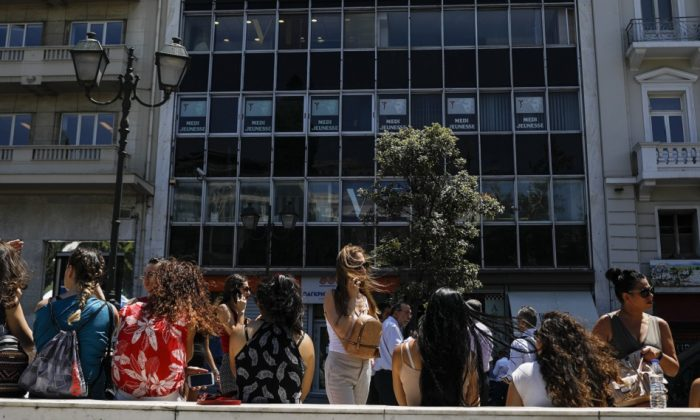 People speak on their phones as they stand outside the building they work in with the Greek, on July 19, 2019. (Petros Giannakouris/AP Photo)