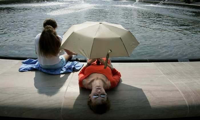 Paige Rose, 12 years-old, and her mother, Cindy Rose, of St. Louis, MO, take shade under an umbrella while they dip their feet in the fountain in the center of the National Gallery of Art Sculpture Garden in Washington on July 26, 2005. (Chip Somodevilla/Getty Images)