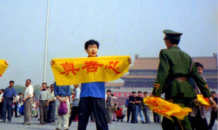 "A Chinese policeman approaches a Falun Gong practitioner at Tiananmen Square in Beijing as he holds a banner with the Chinese characters for ""truthfulness, compassion, and tolerance,"" the core tenets of Falun Gong. (via Minghui.org)"