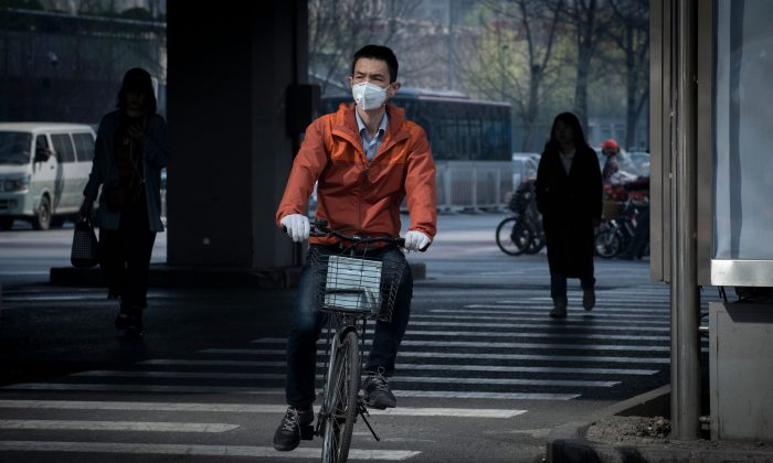 A man riding a bicycle wears a protective mask to reduce the effects of air pollution in Beijing on March 27, 2019. (Nicolas Asfouri/AFP/Getty Images)
