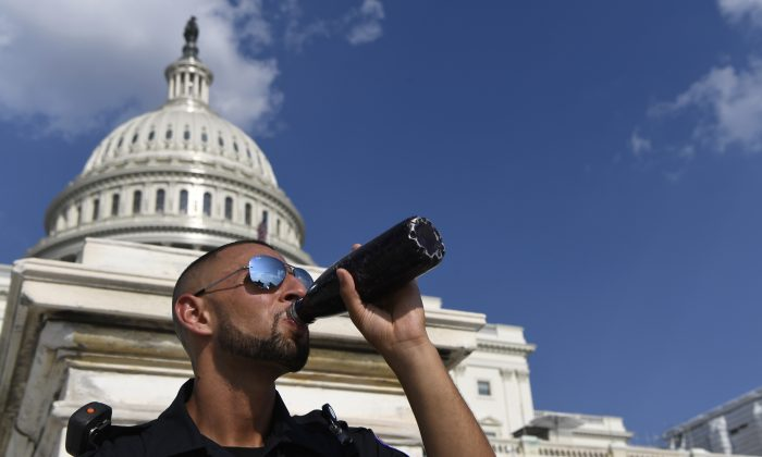 A Capitol Hill police officer takes a drink as he stands his post on the West side of Capitol Hill in Washington, on July 20, 2019. (Susan Walsh/AP Photo)