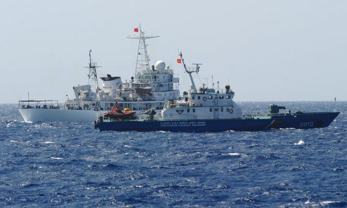 A Chinese coast guard ship (back) sailing next to a Vietnamese coast guard vessel (front), near China's oil drilling rig in disputed waters in the South China Sea, on May 14, 2014. Another dispute between the two countries have recently occurred near an oil block in Vietnam's exclusive economic zone.      (HOANG DINH NAM/AFP/Getty Images)