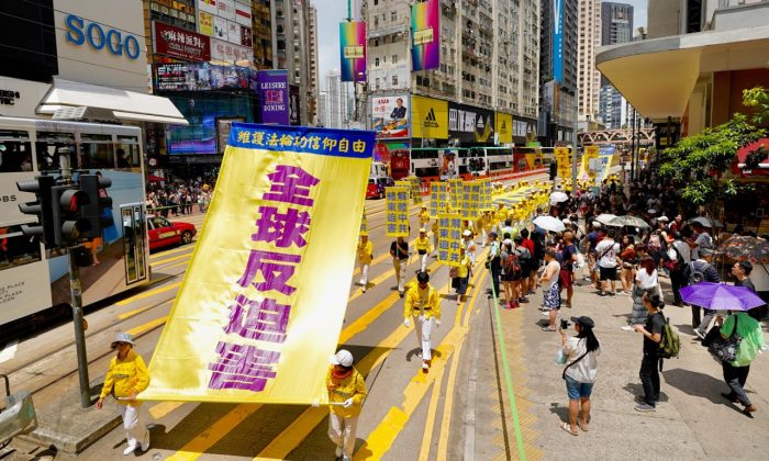 "Falun Gong practitioners hold up a banner with the words ""Global Opposition to Persecution"" in a march in Hong Kong on July 21, 2019. (Li Yi/The Epoch Times)"