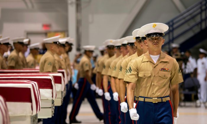 Marines march past transfer cases holding the possible remains of unidentified service members lost in the Battle of Tarawa on July 17, 2019. (Sgt. Jacqueline Clifford/U.S. Marine Corps via AP)