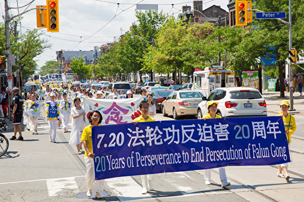 Practitioners of the spiritual practice of Falun Gong march in a parade in Toronto to raise awareness about 20 years of persecution by the Chinese Communist Party, on July 20, 2019. (Wen Ai/The Epoch Times)