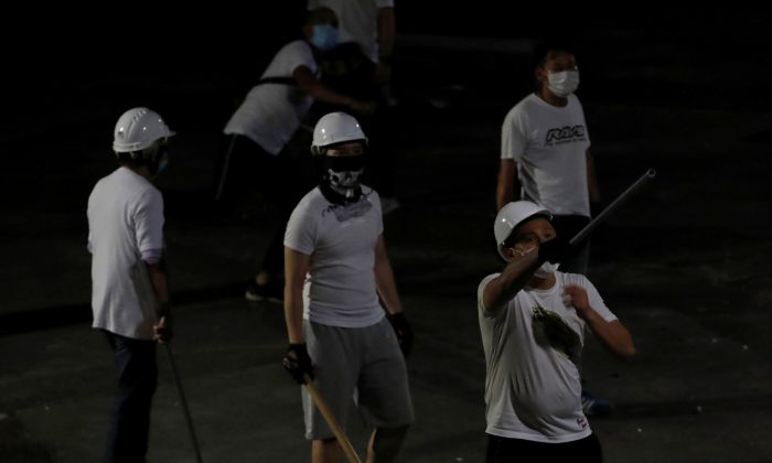 Men in white T-shirts and carrying poles react in Yuen Long after attacking anti-extradition bill demonstrators at a train station in Hong Kong, China on July 22, 2019. (Tyrone Siu/Reuters)