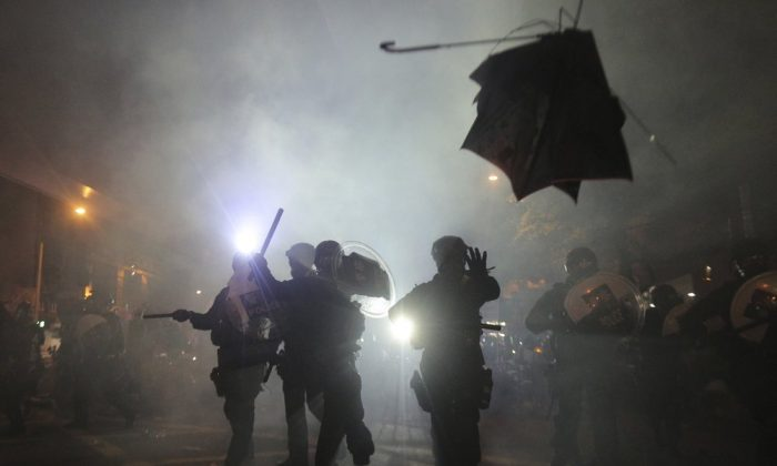 A broken umbrella flies by near riot police, during confrontation with protesters in Hong Kong on July 21, 2019. (Andy Lo/HK01 via AP)