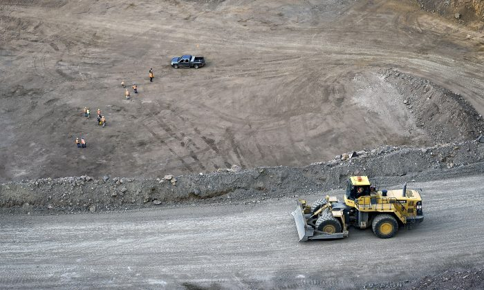 Workers survey the base of the 500-foot-deep open pit at  Molycorp's Mountain Pass Rare Earth facility in Mountain Pass, California on June 29, 2015. (David Becker/Reuters)