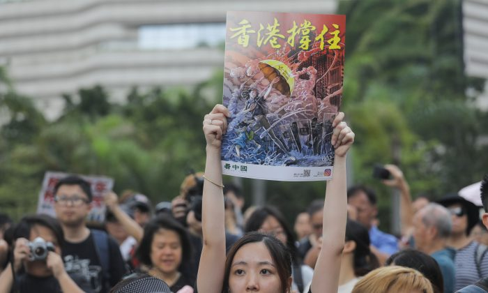 Protesters gather before a march to the West Kowloon railway station holding posters made by Canadian artist Daxiong Guo, during a demonstration against a proposed extradition bill in Hong Kong on July 7, 2019. (Vivek Prakash/AFP/Getty Images)