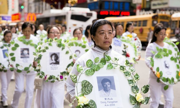 Falun Gong practitioners hold wreaths with photos of people who were killed inside China for their beliefs during a parade in New York City on May 12, 2017. (Samira Bouaou/The Epoch Times)