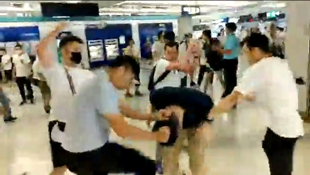 Men in white t-shirts and face masks attack anti-extradition bill demonstrators and reporters at a train station in Hong Kong, on July 21, 2019, in this still image obtained from a social media live video. (Courtesy of Stand News/Social Media via Reuters)