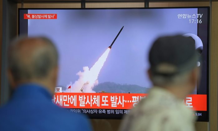 People watch a television news program showing file footage of North Korea's projectile weapons, at a railway station in Seoul on May 9, 2019. (Jung Yeon-Je/AFP/Getty Images)
