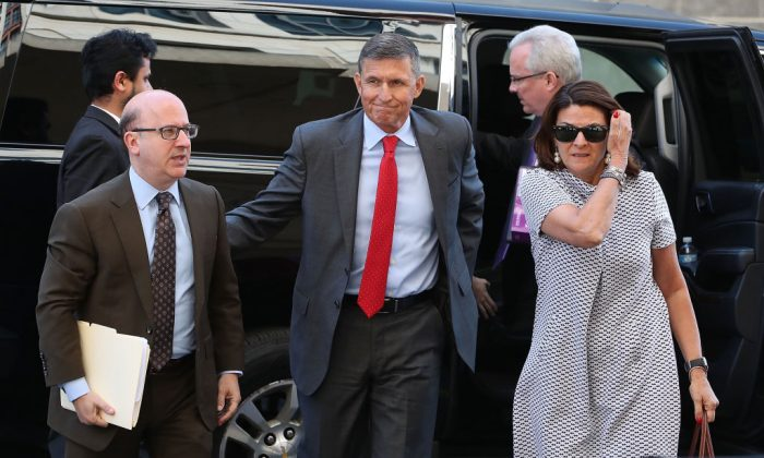 Michael Flynn (C), former national security adviser to President Donald Trump, flanked by lawyers from Covington & Burling, arrives at the E. Barrett Prettyman Federal Courthouse for a status hearing in Washington, on July 10, 2018. (Mark Wilson/Getty Images)