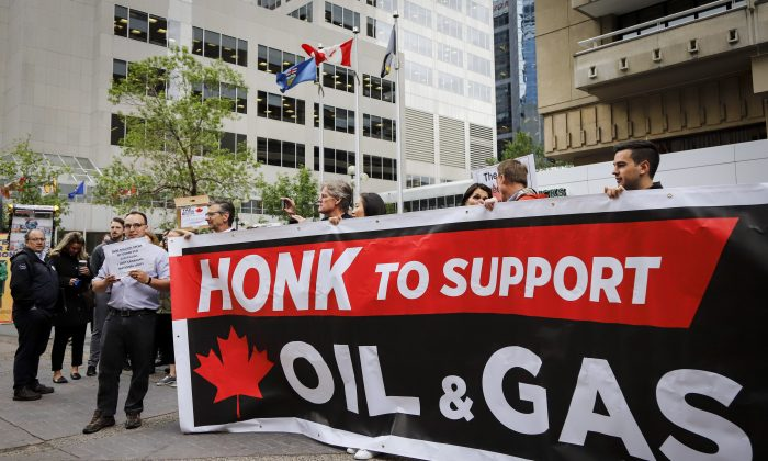 Oil and gas industry supporters rallied outside the venue where Finance Minister Bill Morneau spoke in Calgary on June 19, 2019. Strong political will is needed at all levels of government to curtail regulations that thwart the growth of the oil and gas sector. (The Canadian Press/Jeff McIntosh)