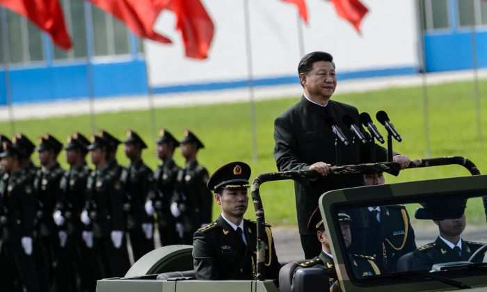 Chinese leader Xi Jinping (R) reviews troops from a car at a garrison of the People's Liberation Army in Hong Kong on June 30, 2017. (ANTHONY WALLACE/AFP/Getty Images)