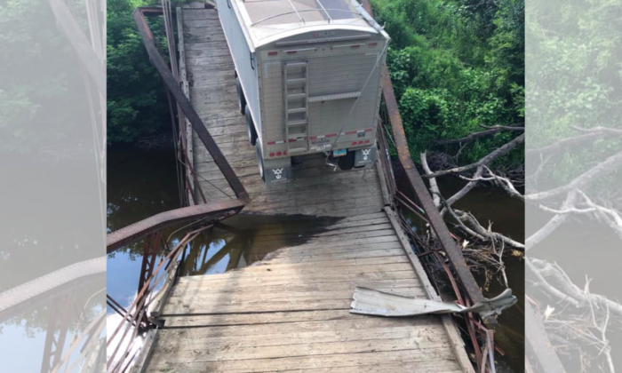 A photo provided by Grand Forks County Sheriff's Department shows an overweight semi has caused the collapse of a small, historic bridge near Northwood, N.D. on July 22, 2019. (Grand Forks County Sheriff's Department via AP)