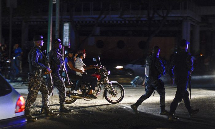 Soldiers and passersby walk in the Petare neighbourhood after Caracas and other parts of Venezuela were hit by a massive power cut on July 22, 2019. (Matias Delacroix/AFP/Getty Images)