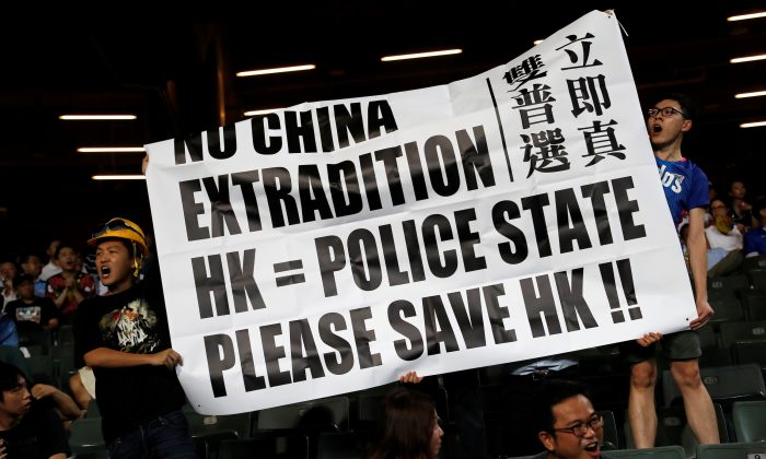 Fans hold an anti-extradition bill banner during a friendly match between Manchester City Football Club and Kitchee, in Hong Kong, China on July 24, 2019. (Tyrone Siu/Reuters)