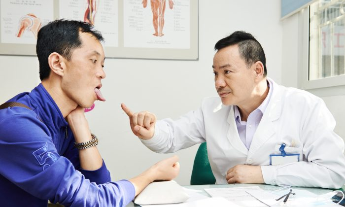 During a traditional Chinese medicine consultation, the doctor may ask to see your tongue to check its color, coating, and whether it is swollen. These qualities can indicate different potential conditions. (Dmitry Kalinovsky/Shutterstock)
