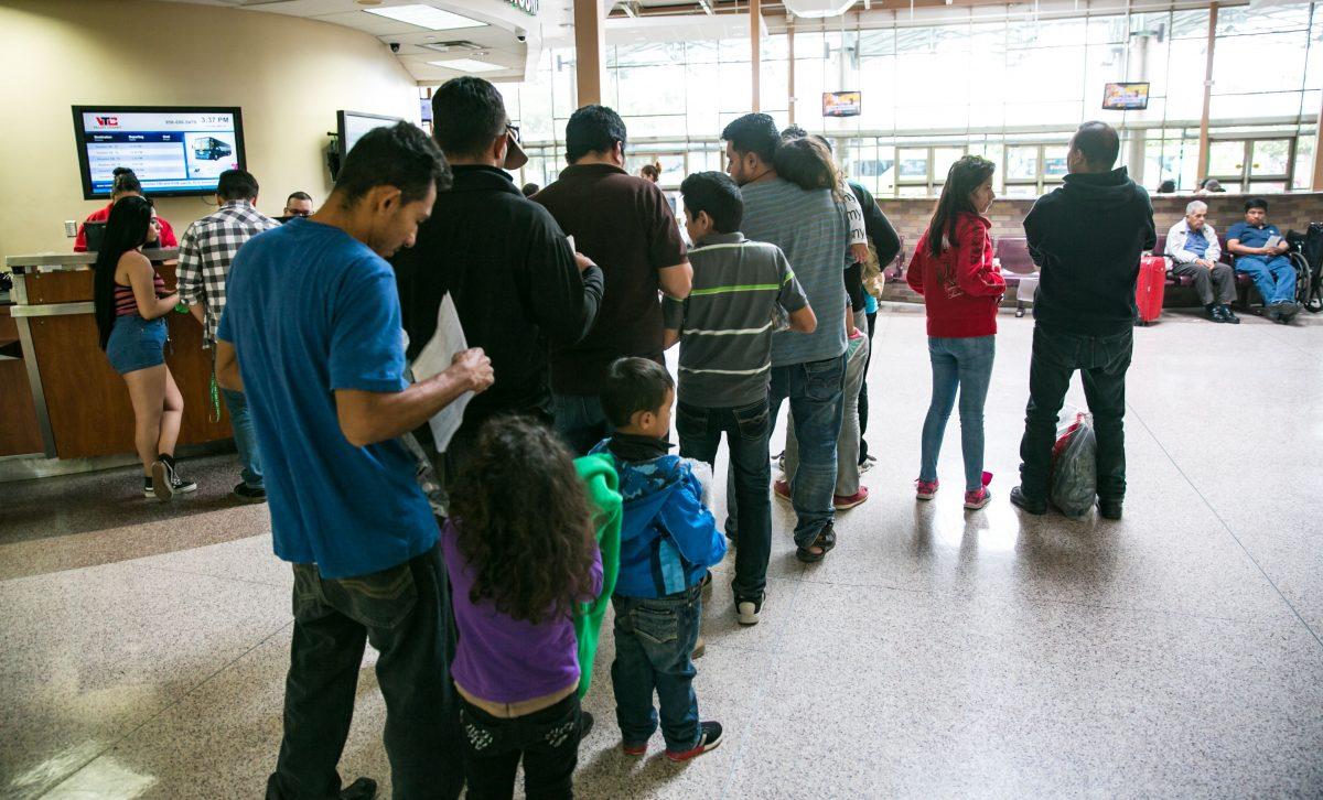 Asylum seekers wait in line to purchase bus tickets in McAllen, Texas