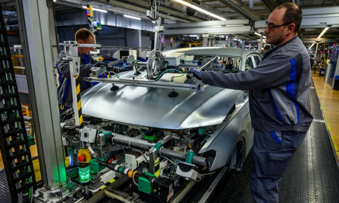 Workers fit a hood on a car on a production line at German car manufacturing giant Volkswagen's headquarters in Wolfsburg, Germany, on March 1, 2019. (John McDougall/AFP/Getty Images)