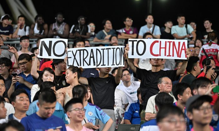 Protesters hold up signs related to the recent political events in the territory, during a football match between English Premier League club Manchester City and Hong Kong side Kitchee at Hong Kong Stadium on July 24, 2019. (Anthony Wallace/AFP/Getty Images)