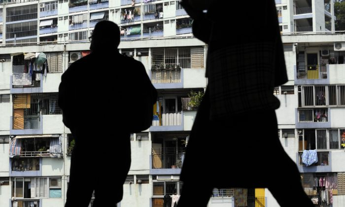A man's silhouette against apartments in China. (Antony Dickson/AFP/Getty Images)