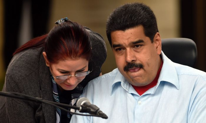 Venezuelan President Nicolas Maduro (R) speaks with First Lady Cilia Flores at Miraflores presidential palace in Caracas on April 7, 2016. (Juan Barreto/AFP/Getty Images)