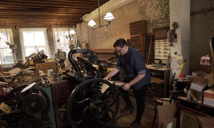 Robert Wilson, art director at Bowne & Co., Stationers on Water Street, operates a letterpress. (Tal Atzmon/NTDTV)