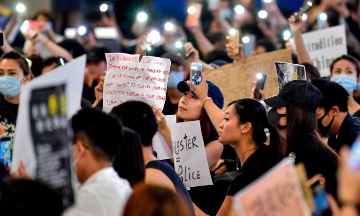 Protesters hold up their mobile phone torches as they rally against a controversial extradition bill at the arrivals hall of the international airport in Hong Kong on July 26, 2019. (Anthony Wallace/AFP/Getty Images)