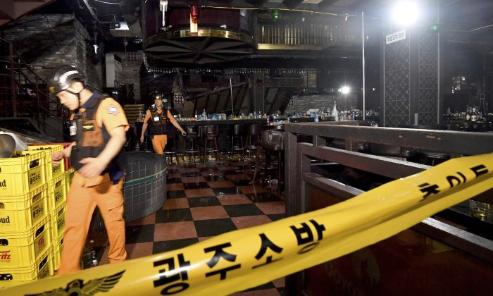 Rescue workers walk to inspect a collapsed internal balcony at a nightclub in Gwangju, South Korea, on July 27, 2019. (Shin Dae-hee/Newsis via AP)