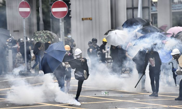 Anti-riot police fire tear gas at protesters during a demonstration in the district of Yuen Long in Hong Kong on July 27, 2019. The protesters were marching through a Hong Kong town near the Chinese border to rally against suspected triad gangs who beat up pro-democracy demonstrators there the previous weekend.  (Anthony WallaceE/AFP/Getty Images)
