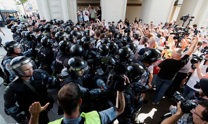 Law enforcement officers block protesters during a rally calling for opposition candidates to be registered for elections to Moscow City Duma, the capital's regional parliament, in Moscow, Russia, on July 27, 2019. (Reuters/Shamil Zhumatov)