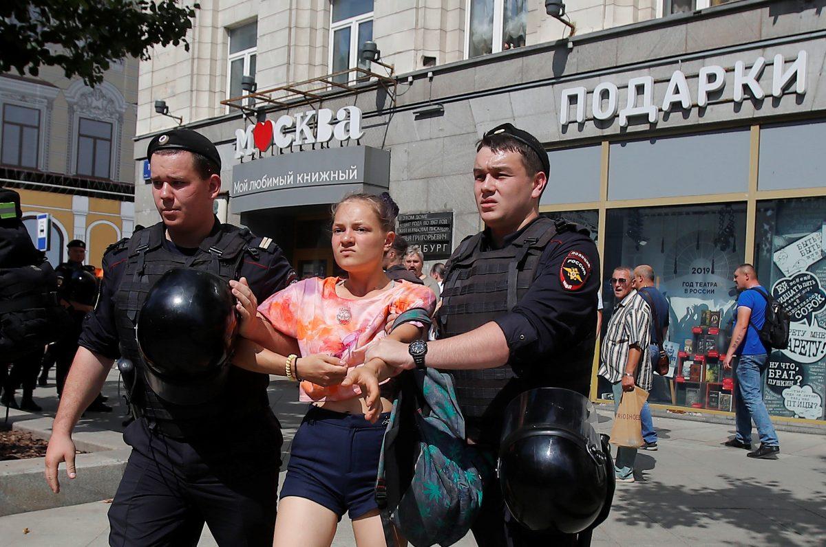 Law enforcement officers detain a woman