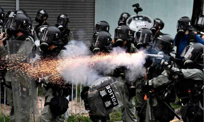 A policeman fires tear gas to disperse protesters during a demonstration in the district of Yuen Long in Hong Kong on July 27, 2019. (Anthony Wallace/AFP/Getty Images)