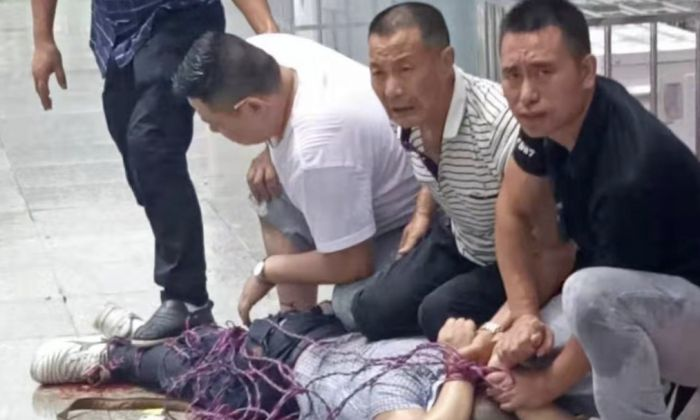 Xu Weigang was controlled by village officials after he made the blasts on July 26, 2019. (Provided to The Epoch Times by interviewee)