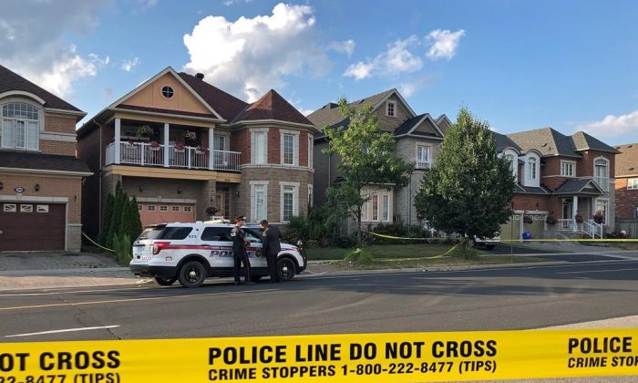 York Regional police officers stand outside of a home in Markham, ON. on July 28, 2019. Police say one person is in custody after four bodies were found in a home north of Toronto. (Alanna Rizza/The Canadian Press)