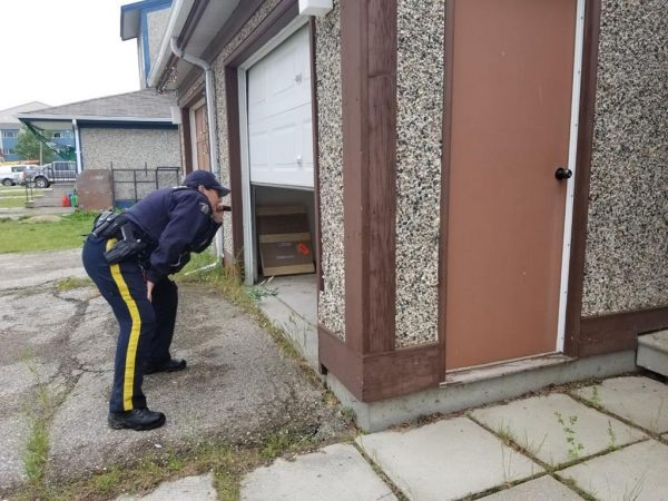 An RCMP officer shines a light into an open garage at a home in the Gillam, MB., area in July 27, 2019, police image published to social media. (HO-Twitter, Royal Canadian Mounted Police, @rcmpmb/The Canadian Press)