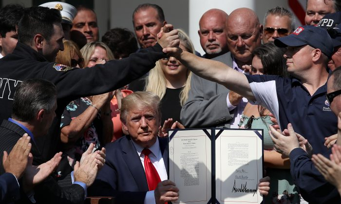 As first responders and their families celebrate, President Donald Trump shows his signature on H.R. 1327, an act to permanently authorize the Sept. 11 victim compensation fund, in the Rose Garden of the White House in Washington on July 29, 2019. (Win McNamee/Getty Images)