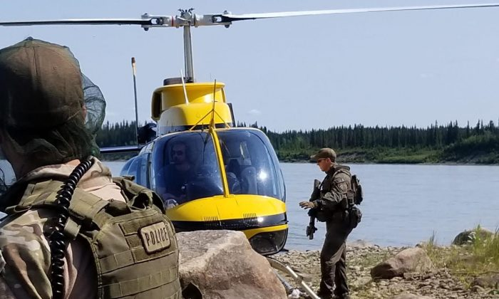 RCMP officers work near a helicopter responsible for aerial search. The force has announced that they will withdraw their resources from York Landing, Manitoba, after an unsuccessful attempt to locate two B.C. murder suspects. (Royal Canadian Mounted Police)