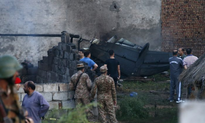 Pakistan army officials examine the site of a plane crash in Rawalpindi, Pakistan on July 30, 2019. (Anjum Naveed/AP Photo)