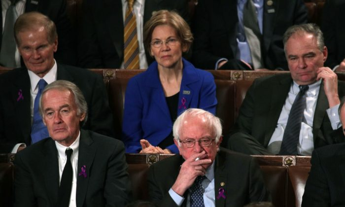 Sens. Elizabeth Warren (D-Mass.) and Bernie Sanders (I-VT) (C) watch during the State of the Union address in the chamber of the U.S. House of Representatives in Washington, on Jan. 30, 2018. (Alex Wong/Getty Images)
