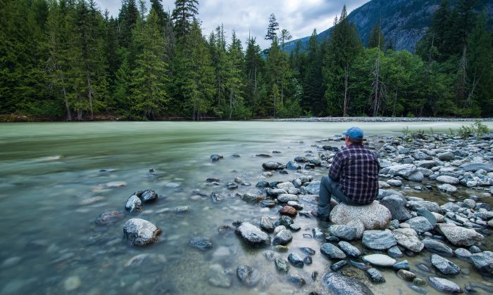 A man sits quietly by a river in British Columbia, Canada. Taking no action is sometimes the best thing you can do. (James Wheeler/pixabay.com)