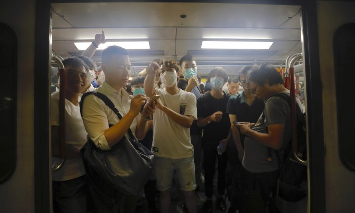 Protesters wearing masks occupy a train car at a subway station in Hong Kong on July 30, 2019. Protesters in Hong Kong have disrupted subway service during the morning commute by blocking the doors on trains, preventing them from leaving the stations. (Vincent Yu/AP)